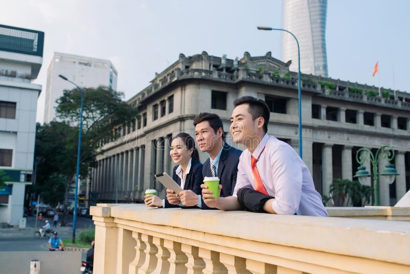 Asian business woman and men having coffee break outside in front of building royalty free stock photo