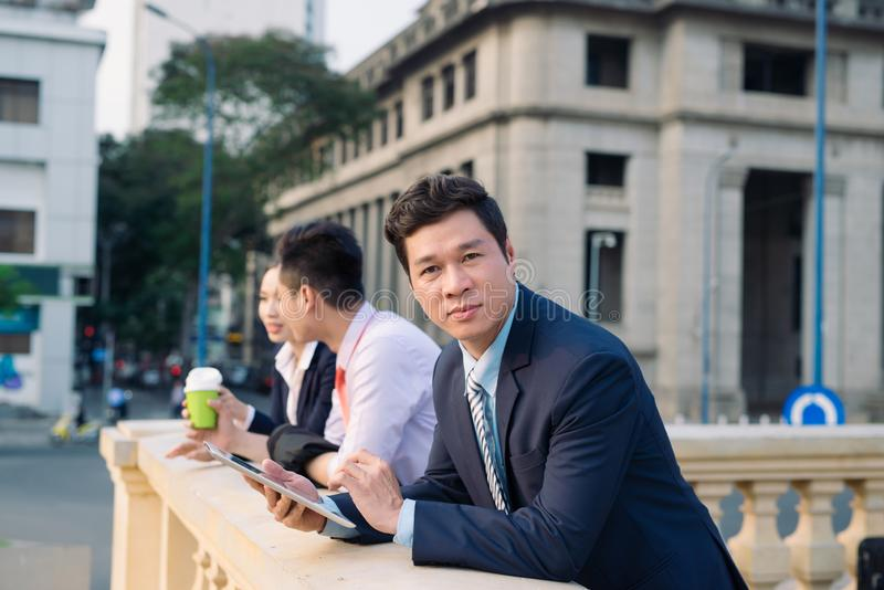Asian business woman and men having coffee break outside in front of building stock photos