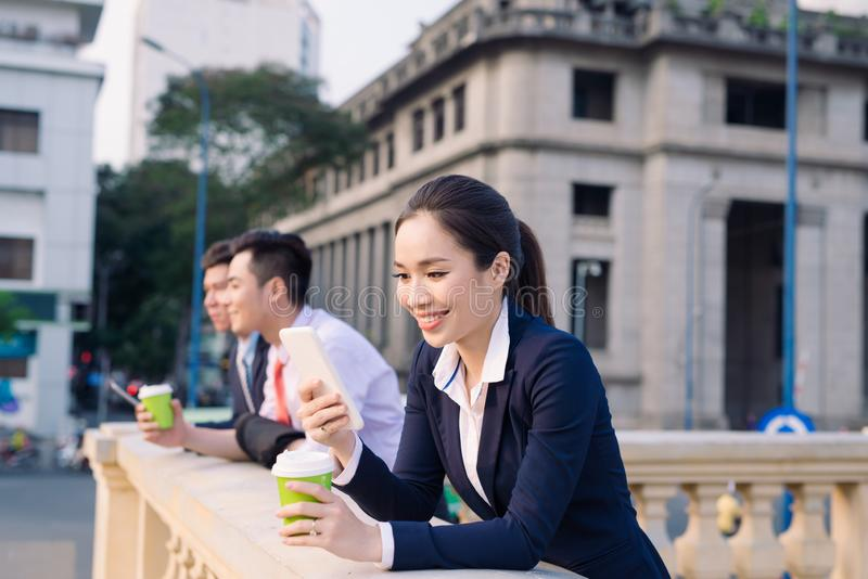 Asian business woman and men having coffee break outside in front of building stock images