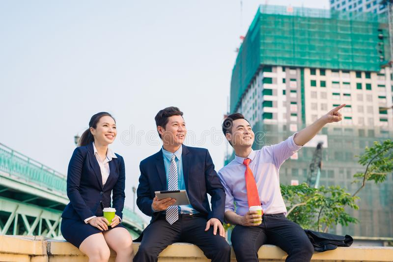 Asian business woman and men having coffee break outside in front of building stock photo