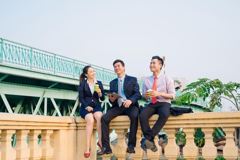 Asian business woman and men having coffee break outside in front of building royalty free stock image