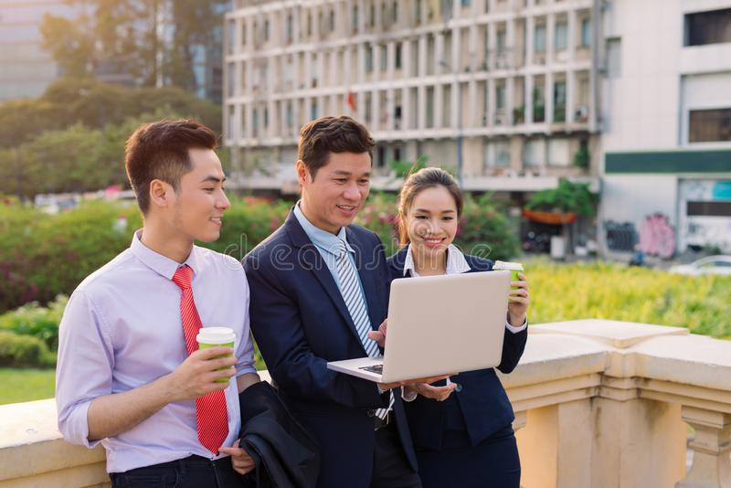 Asian business woman and men working outside on computer royalty free stock photography
