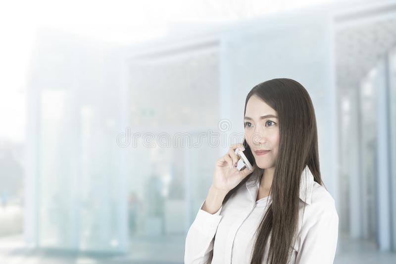 Asian business woman office worker communicating with mobile phone. Asian business woman office worker communicating with mobile phone on blurred background stock images