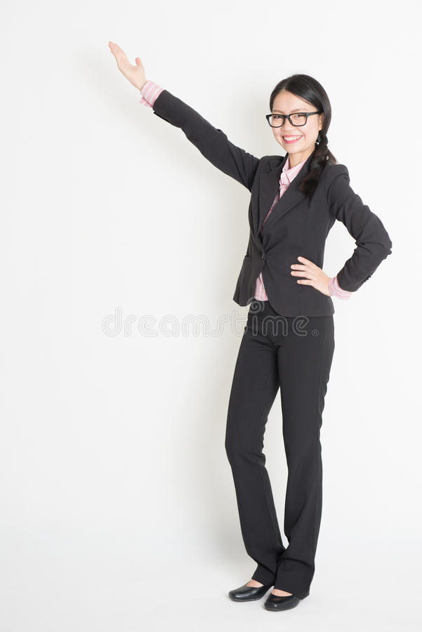 Asian business woman pointing. Full body Asian business woman showing copy space, standing on plain background stock photography