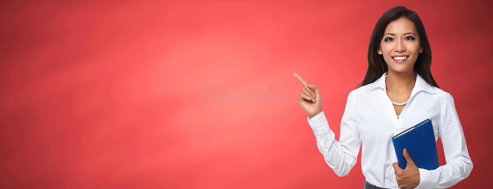 Asian business woman presenting copy space. Beautiful asian business woman over red background royalty free stock photography