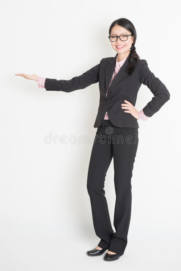 Asian business woman showing copy space. Full body Asian business woman showing copy space, hand holding something, standing on plain background royalty free stock photography