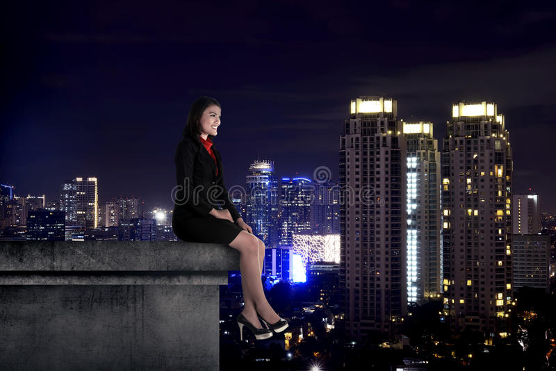 Asian business woman sit on the building rooftop. At night time stock images