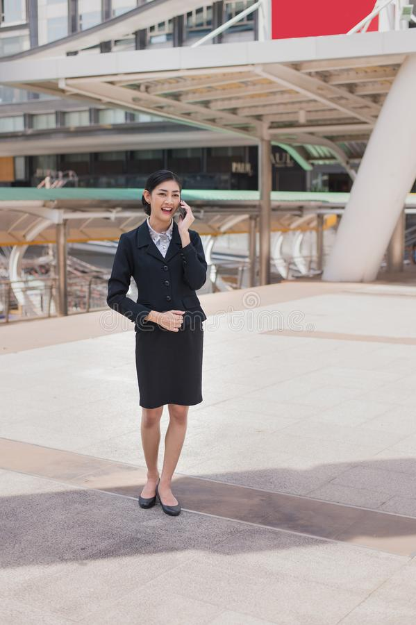 Asian business woman smile and hold cell phone to talk about business success. Asian business woman wear black suit, she smile and hold cell phone to talk about stock photos