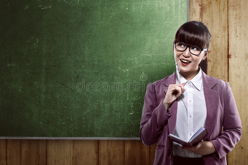 Asian business woman smiling over empty blackboard. Asian business woman smiling over empty whiteboard. You can put your message on the board stock photo