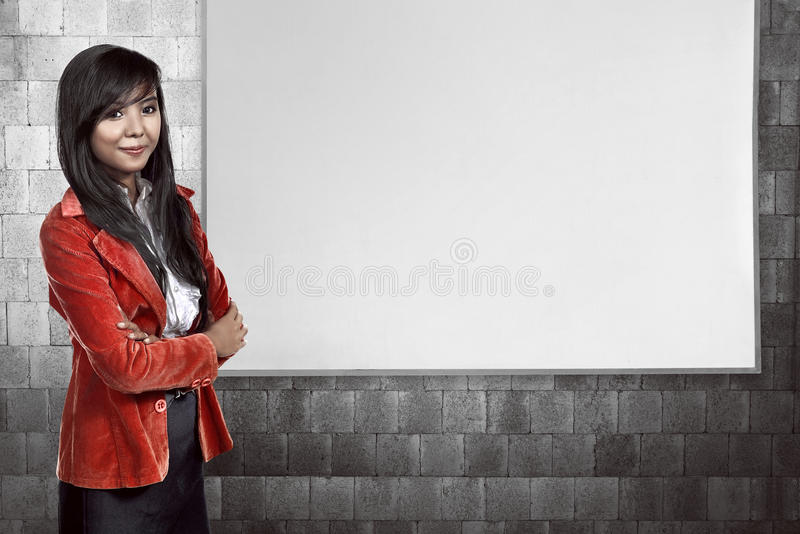 Asian business woman smiling over empty whiteboard. You can put your message on the board stock image