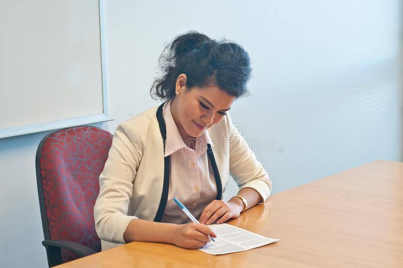 Business woman signing contract agreement in office. Asian business woman is smiling while signing a contract agreement in the office stock photography