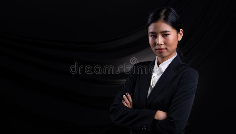 Asian Business Woman Stand in dark Formal Suit. Portrait Asian Business Woman dark blue Formal proper Suit, studio lighting black drape fabric background royalty free stock image