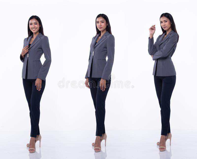 Asian Business Woman Stand in White Formal Suit. Full Length Snap Figure, Asian Business Woman Stand in Blue Formal proper Suit pants and high heel shoes, studio royalty free stock photo
