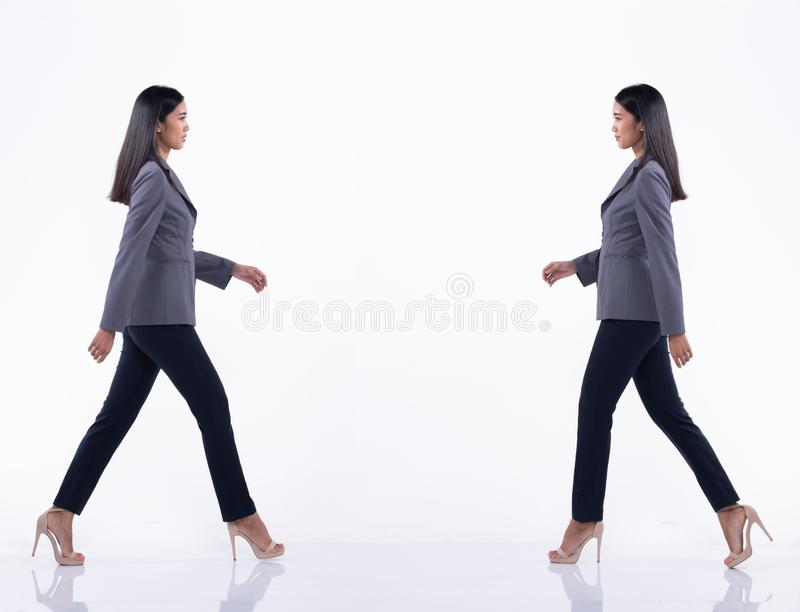 Asian Business Woman Stand in White Formal Suit. Full Length Snap Figure, Asian Business Woman walks in Blue Formal proper Suit pants and high heel shoes, studio stock image