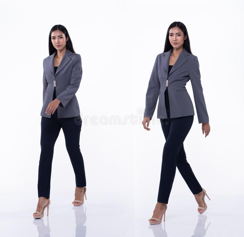 Asian Business Woman Stand in White Formal Suit. Full Length Snap Figure, Asian Business Woman walks in Blue Formal proper Suit pants and high heel shoes, studio royalty free stock image