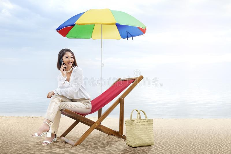 Asian business woman talking on mobile phone while sitting sitting in the beach chair with colorful umbrella on beach. Summer vacation stock photos