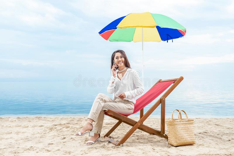 Asian business woman talking on mobile phone while sitting sitting in the beach chair with colorful umbrella on beach. Summer vacation royalty free stock photography
