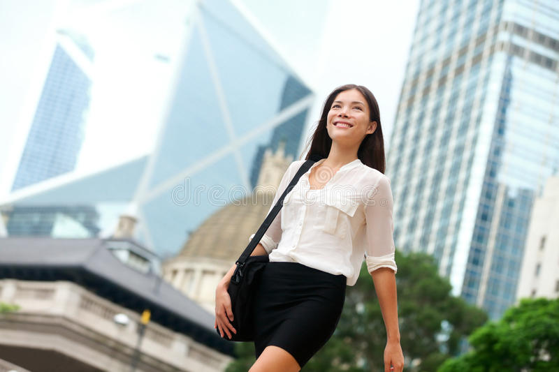 Asian Business woman walking outside in Hong Kong. Asian businesswoman office worker in downtown business district. Young multiracial Chinese Asian / Caucasian royalty free stock images