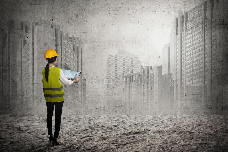 Asian business woman wear yellow helmet looking blueprint to build office building royalty free stock photo