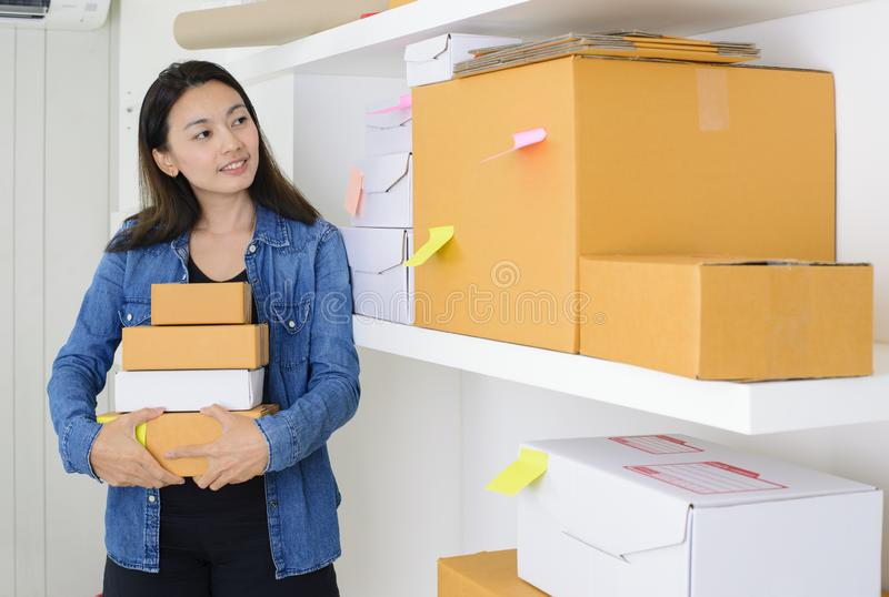 Asian business woman work at home office checking order ready to mailing or shipping with boxes and sticky note paper.  royalty free stock images