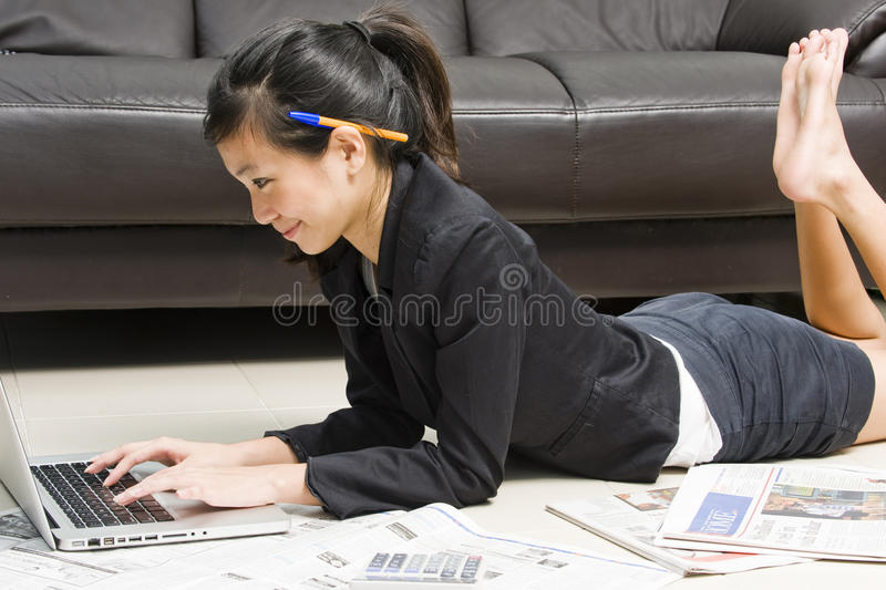 Asian business woman working from home. Asian business woman working comfortably from home, only dressing her top formally royalty free stock photo