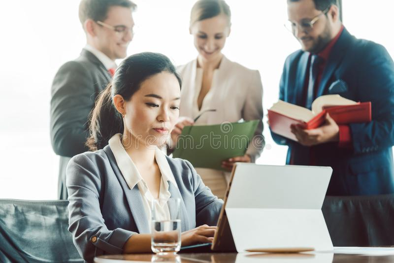 Asian business woman working on laptop with colleagues in background stock image