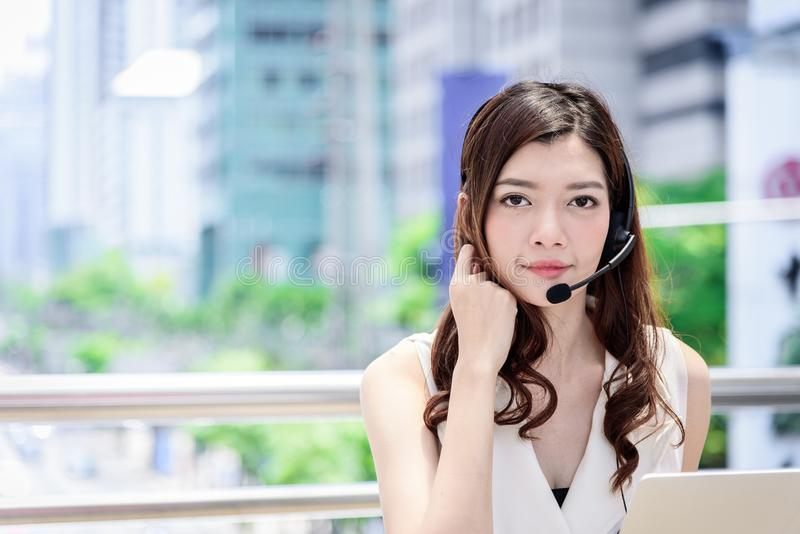 The asian business woman working and operation in outside office with building and city background stock image