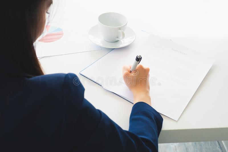 Asian business woman writing signature in document royalty free stock images