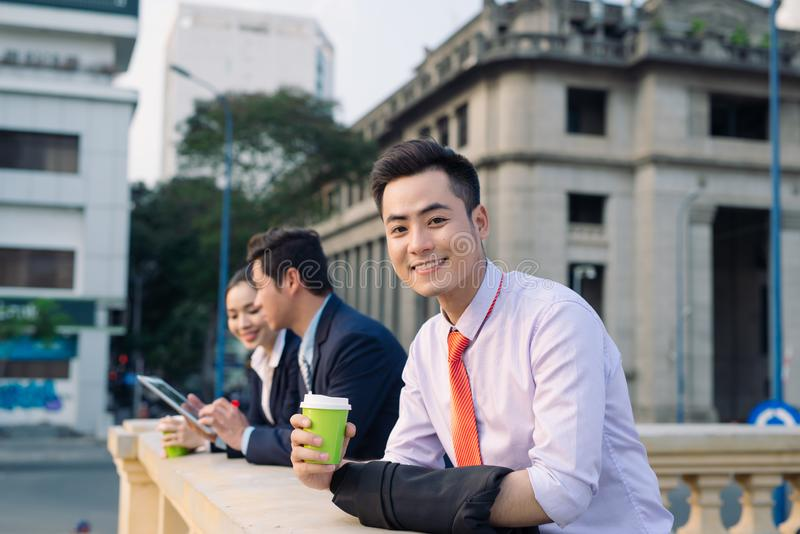 Asian business woman and men having coffee break outside in front of building stock image