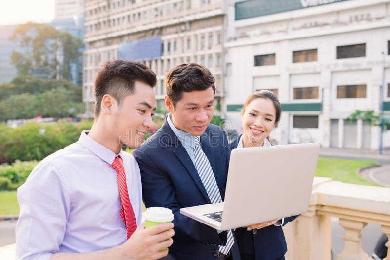 Asian business woman and men working outside on computer royalty free stock image