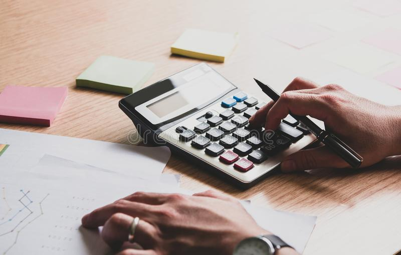 Asian business young man working ,using calculator Calculate tax lead to liquidation, With Sunset light vintage style royalty free stock photography