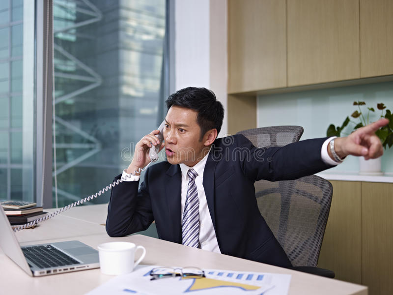 Asian businessman. Talking on phone in office, looking angry stock photography