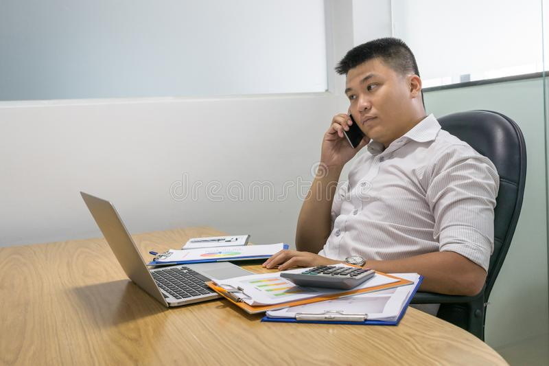Asian businessman answer the phone call in office royalty free stock photo