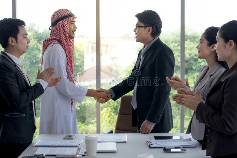 Asian businessman and Arabian businessman success in the deal shaking hands with business people clap their hands royalty free stock photo