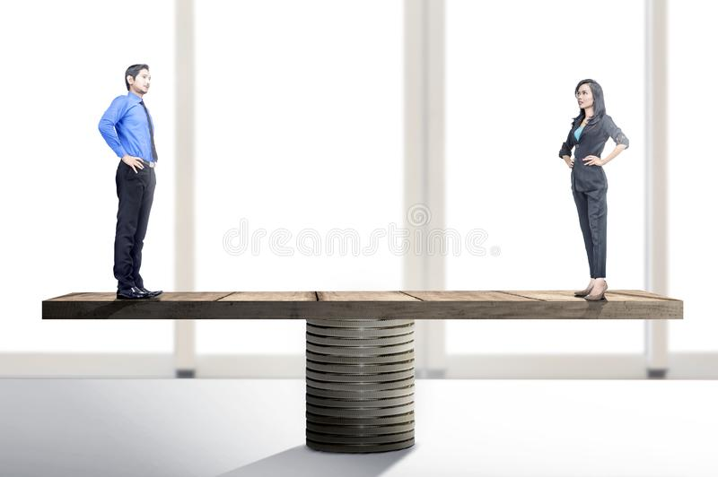 Asian businessman and businesswoman standing on balancer. Equality gender concept royalty free stock image