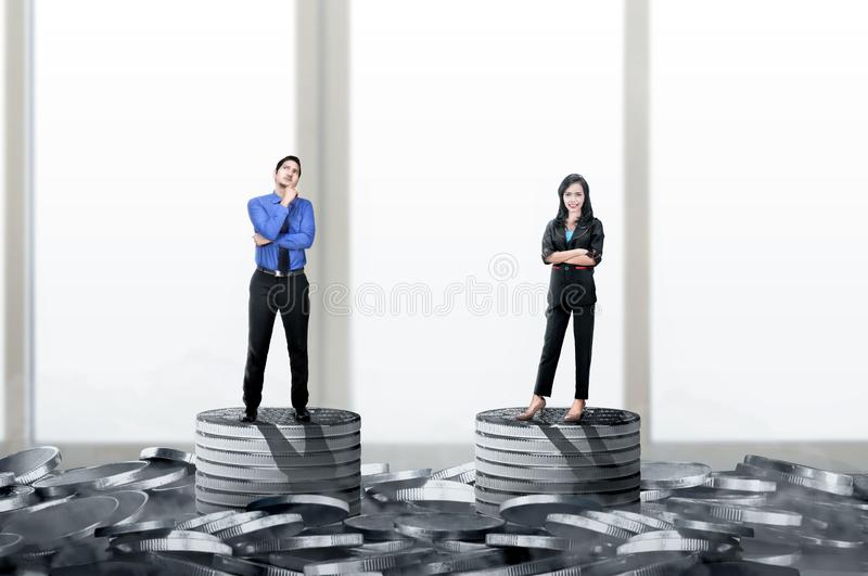 Asian businessman and businesswoman standing on the coins stack with same height. Equality gender concept stock photography