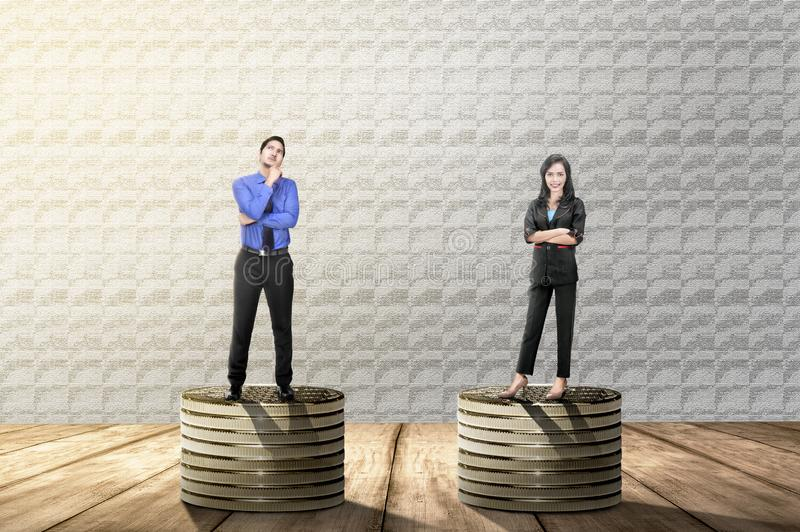 Asian businessman and businesswoman standing on golden coins stack with same height. Concept of gender equality royalty free stock photo