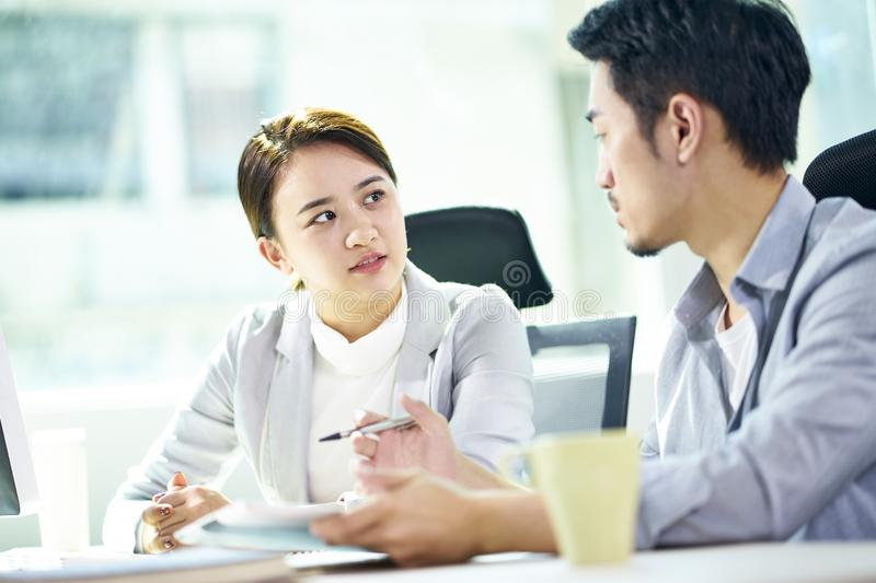 Asian businessman and businesswoman working together in office stock images