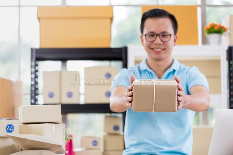 Asian businessman in casual shirt hold in parcels on hand, working in simple house office look like doing startup business. royalty free stock photos