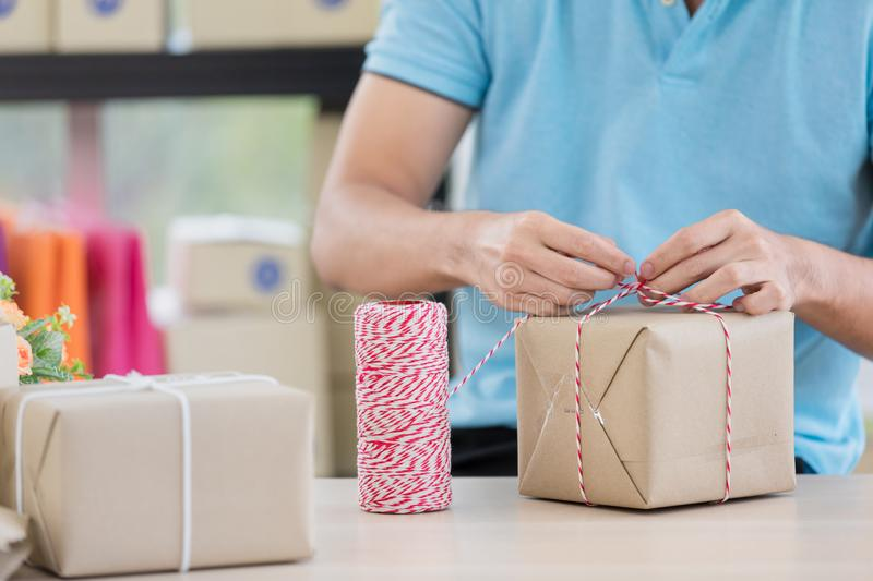 Asian businessman in casual shirt was is packing parcels, working in simple house office look like doing startup business. stock photo