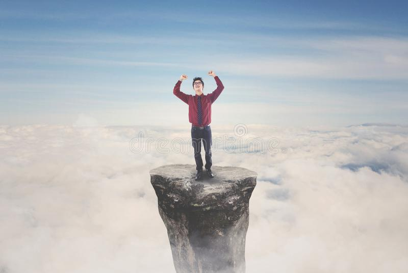 Asian businessman celebrating his success on mountain. Image of Asian businessman celebrating his success by lifting hands while standing on the mountain top stock image