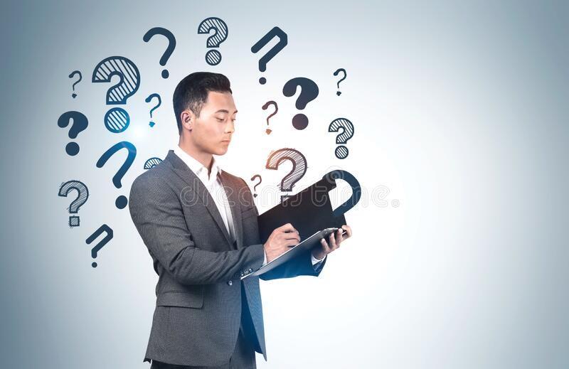 Asian businessman with clipboard, question marks royalty free stock images