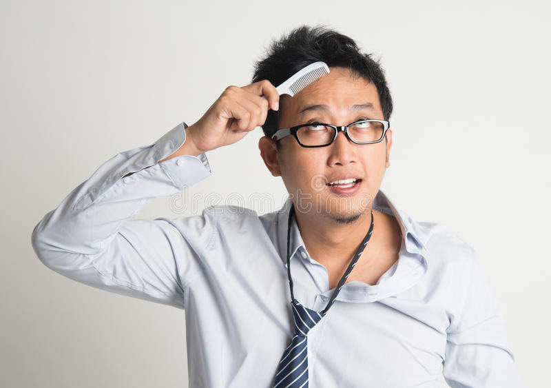 Asian businessman combing hair. In morning in hurry, on plain background royalty free stock photos
