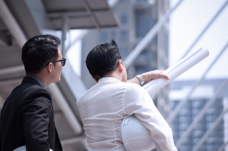 Asian businessman discuss with engineer architect in suite, look. Ing and point to finger forward away and holding construction roll plan for working team stock photography