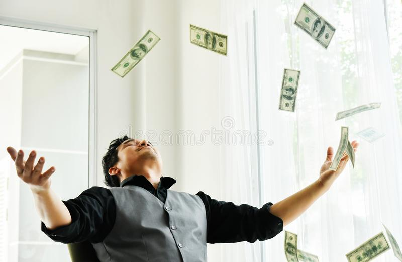 Happy male in a rain of money. Asian businessman with dollar bills cash falling down. Success economy concept. Happy male in a rain of money stock photography