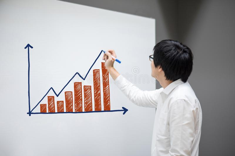 Asian businessman drawing bar chart and graph. Asian businessman with glasses drawing bar chart and graph on white board in office meeting room for business stock image