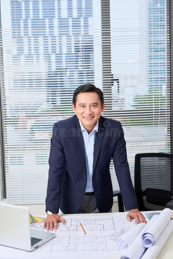 Asian businessman, an engineer with the work plan, standing in t. He office stock image