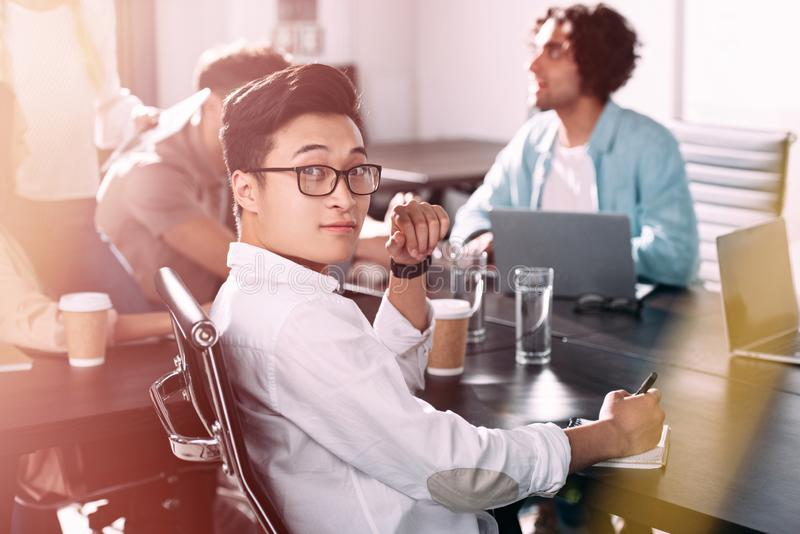 asian businessman in eyeglasses looking at camera while his partners having discussion at modern stock images