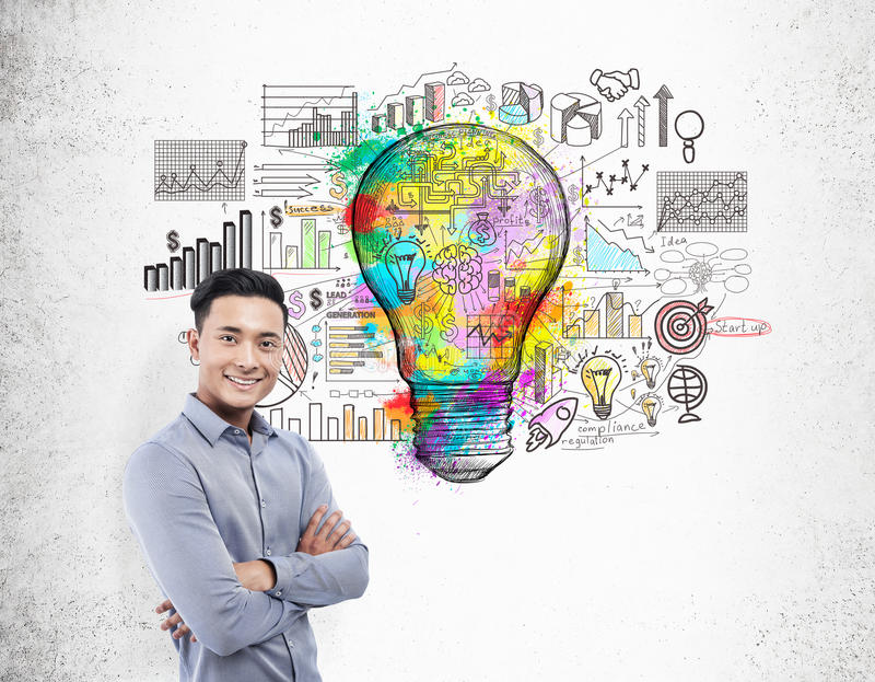 Asian businessman with giant colorful light bulb sketch. Portrait of smiling Asian businessman standing near colorful light bulb sketch surrounded by graphs on royalty free stock images