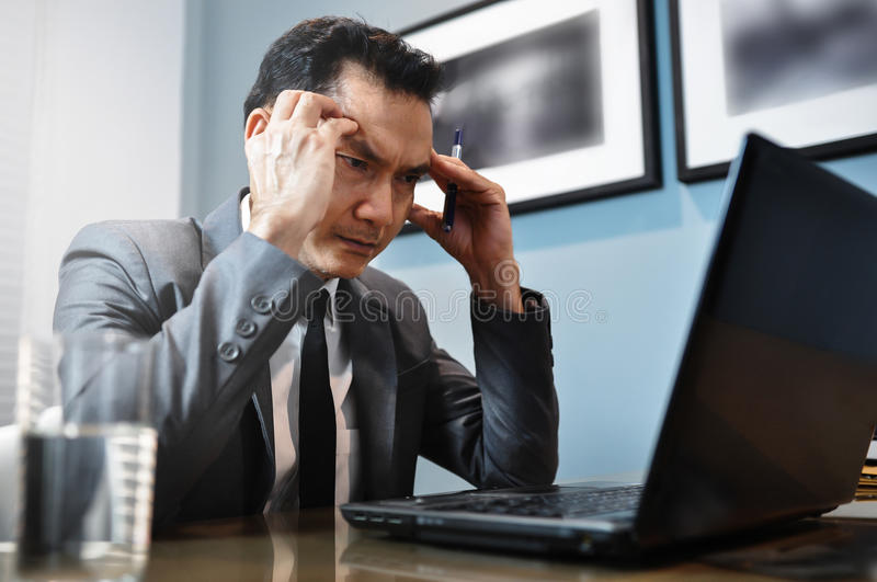 Asian Businessman in grey suit thinking and looking to his laptop. Man has stressed and headache from migraine. stock photo